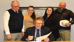 """Warwick Lorenz signs on behalf of """"Team Australia"""" for the MoU."""
